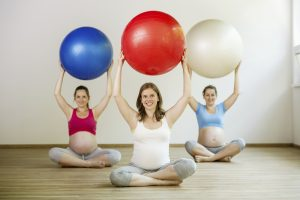 Young pregnant women doing relaxation exercise using a fitness ball